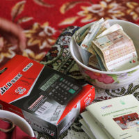 A calculator, bowl of money, and record book are used by the community-based savings group.